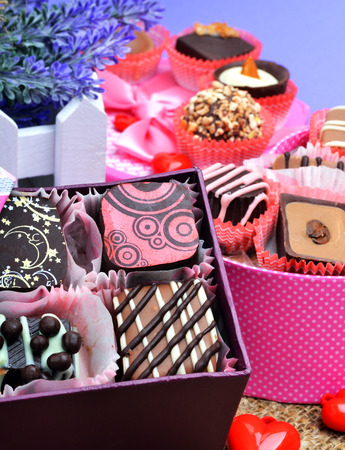 Assortment of chocolate sweets in gift boxes, lavender on blue background photo