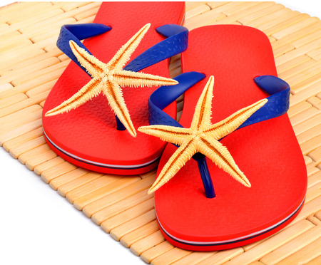 Red flip-flops, slippers with starfish on the wooden background isolated on white photo