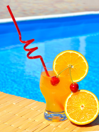 pool party: Cocktail glass with orange and cherry on pool background Stock Photo