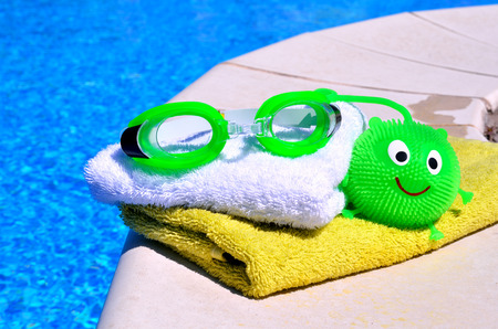 swimming pool: bath towels, goggles, toy against blue wate Stock Photo