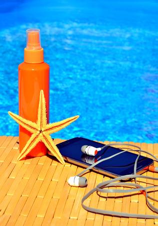 ear phones: Cell phone, sun spray, head phones and starfish near blue water