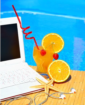 pool party: Cocktai with fruits, laptop and starfish on pool background