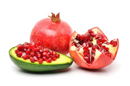 a pomegranate: Ripe pomegranate, avocado, pomegranate seeds on white background