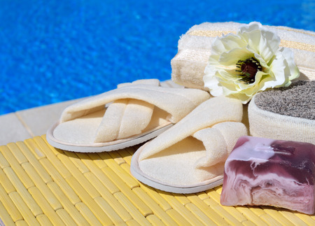 handmade soap: Natural bath sponges, bath slippers, handmade soap and flower on a wooden background on the swimming pool