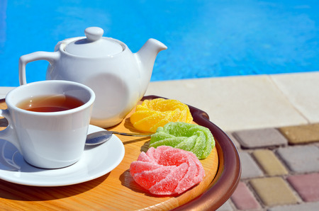 british ethnicity: Cup of tea on a sauce, teapot and colored marmalade beside the pool.