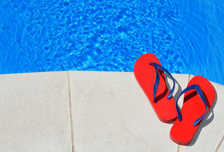diving pool: Pair of red flip-flops on the swimming pool