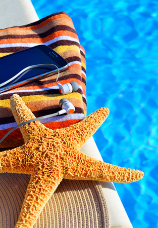 Beach hat, bath towels, cell phone, starfish near the swimming pool