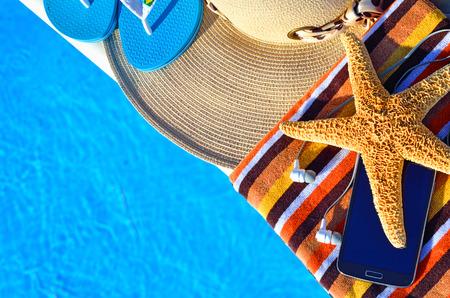 thong: Beach hat, bath towels, cell phone, starfish, thongs near the swimming pool