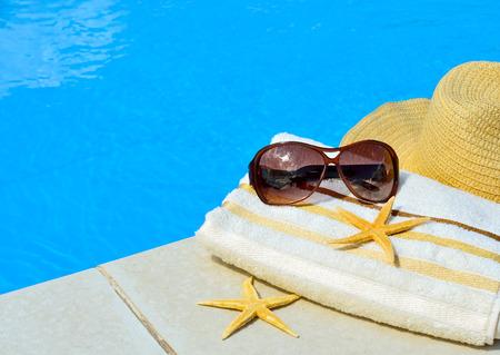 bath towel: Beach hat, sunglasses, bath towel, starfish near the swimming pool