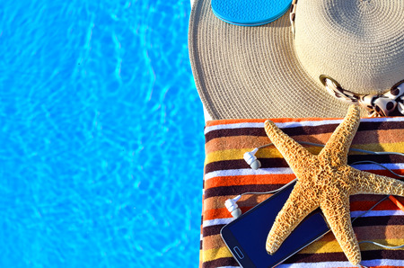 stella marina: Cappello della spiaggia, teli da bagno, telefono cellulare, stelle marine nei pressi della piscina