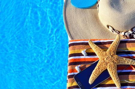 étoile de mer: Chapeau de plage, serviettes de bain, téléphone cellulaire, étoiles de mer près de la piscine Banque d'images