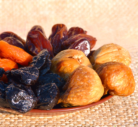 sacking: Dried fruit, dates, figs, prunes, apricots on the plate on the sacking background Stock Photo
