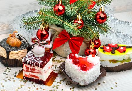 porcion de pastel: Deliciosos pasteles de Navidad en el fondo de Navidad, bolas de Navidad, ramita de pino.