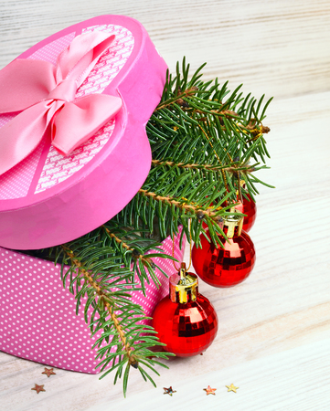 pinetree: Gift box with christmas baubles and pinetree on a wooden background