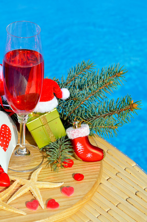 party food: Glasses with red champagne  and Christmas decor on swimming pool background
