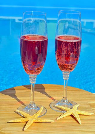 water  pool: Two glasses of sparkling red wine and  starfish on a background of pool Stock Photo