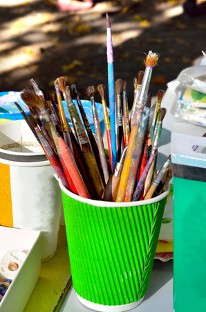 artist: Paint brushes in a glass on the table