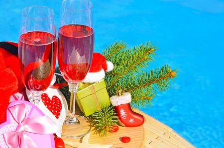 party decoration: Glasses with red champagne  and Christmas decor on swimming pool background