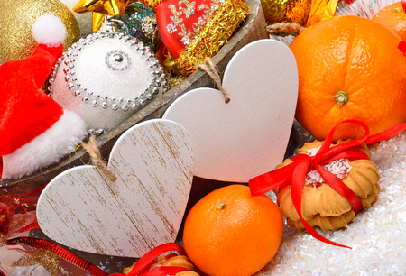 for text: Christmas decoration, pine twig, card for text, christmas baubles, sweetness and mandarins on red background