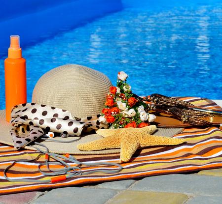 head phones: Beach hat, flip flops, head phones, sun spray on the beach. Stock Photo