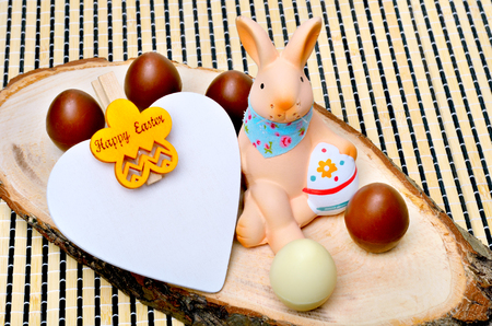 chocolate eggs: Easter decoration  bunny with chocolate eggs on wooden background.