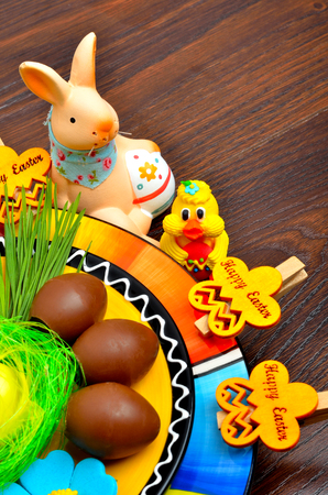 chocolate eggs: Easter decoration  bunny with chocolate eggs on a colored plate. Stock Photo
