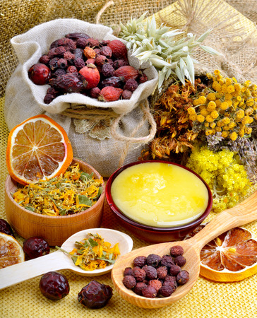 medicinal herbs: Medicinal herbs with honey, calendula, oats, immortelle flower, tansy herb. Stock Photo