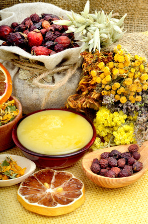 medicinal herbs: Medicinal herbs with honey, calendula, oats, immortelle flower, tansy herb, wild rose. Stock Photo