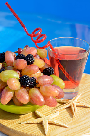 blue hawaiian drink: Fruit cocktail with grapes, blackberries and starfish on a background of the pool.