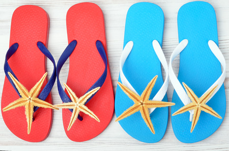 flipflops: Flip-flops and starfish on a wooden background.