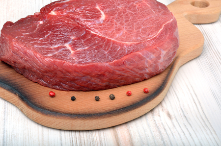 pungent: Raw beef steak with red pepper, on a cutting board. Stock Photo