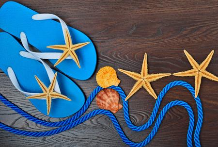 flipflops: Flip-flops, starfish and seashells on a wooden background.