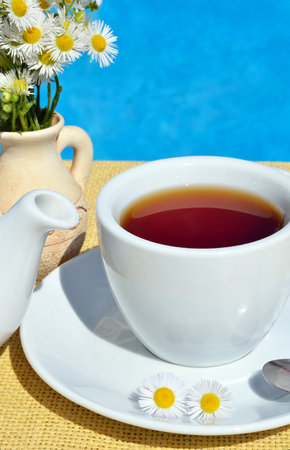 Black tea in a cup in front of the pool.