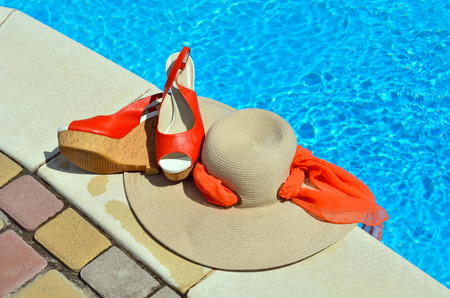 Woman beach hat,  red sandals and starfish on the pool background.