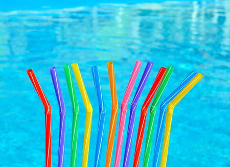 Colored tubules for juice and cocktail on the background of the pool.