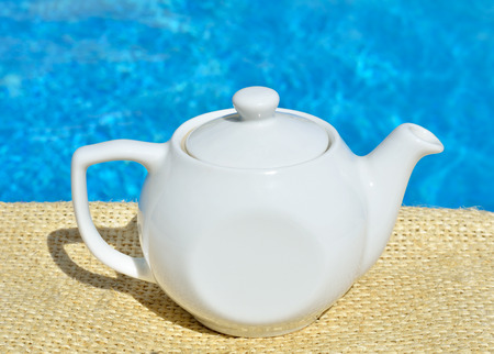 Tea teapot on a swimmimg pool background.