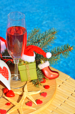 Christmas decoration and Glasses with red champagne on swimming pool background.
