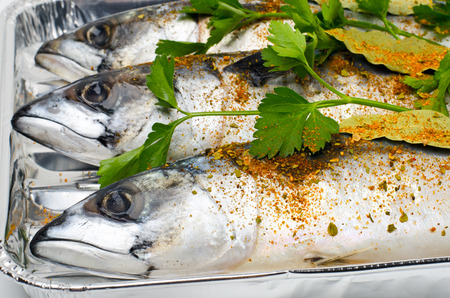 Mackerels with spices and parsley on the foil for baking. Standard-Bild