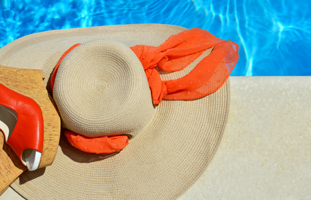 woman sandals: Woman beach hat and red sandals on the pool background. Stock Photo