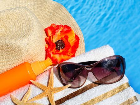 Beach hat, sunglasses, bath towel, sun spray, starfish near the swimming pool