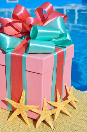 Gift box against with starfish the background of the blue pool. Standard-Bild