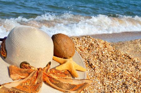 Women's hat, coconut and starfish on the beach. Standard-Bild