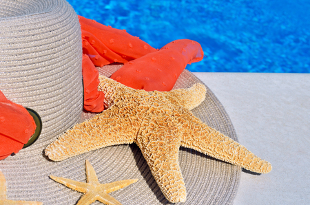 Woman beach hat and starfish on the pool background.