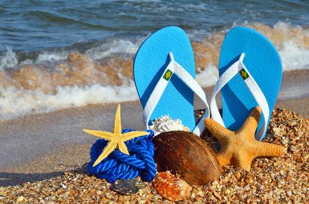 Bunte Flipflops, Starfish, Kokosnuss und Seil am Strand. Standard-Bild - 72065600
