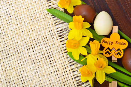 Easter decoration, fresh spring narcissus flowers and chocolate eggs.