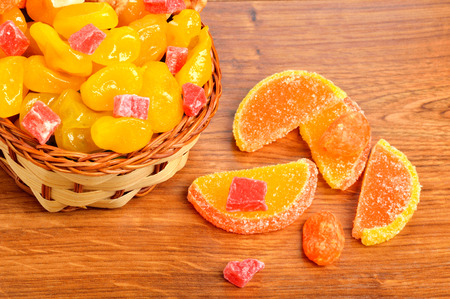 colorful candies and jellies in basket on wooden background Standard-Bild