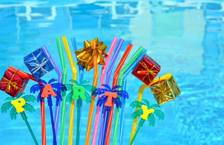 Party decorations and colored tubuleson the swimming pool background.