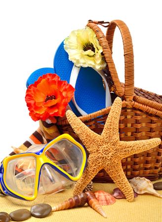 Flip-flops, fishstar, wicker basket, goggles isolated on white.