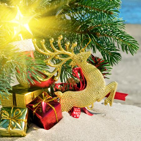 Christmas toys, reindear and christmas tree on sea background. Standard-Bild