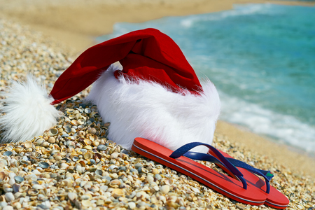 Santa Claus hat and flip flops оn sand on the sea background.